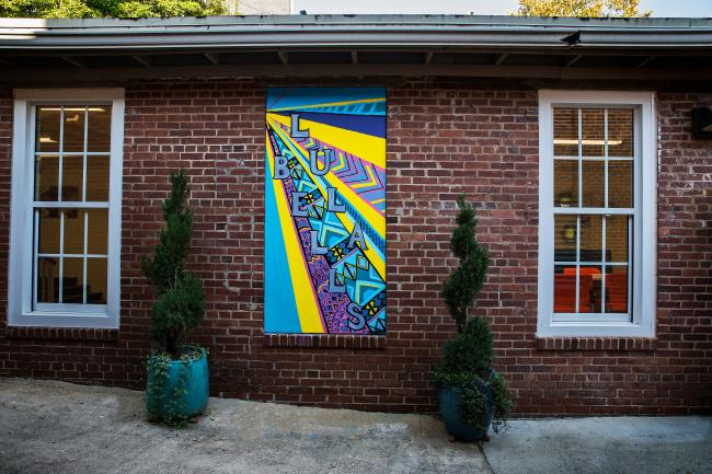 Lula Bell's entryway with graffiti mural and planters against brick exterior