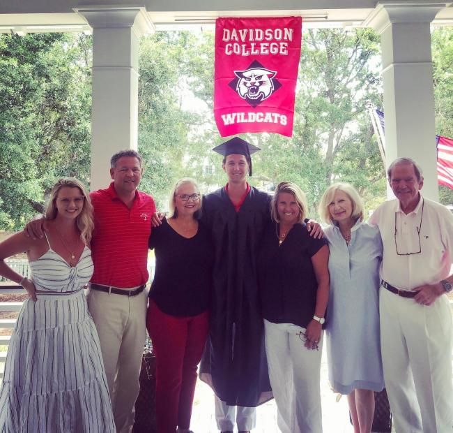 graduate stading with his family