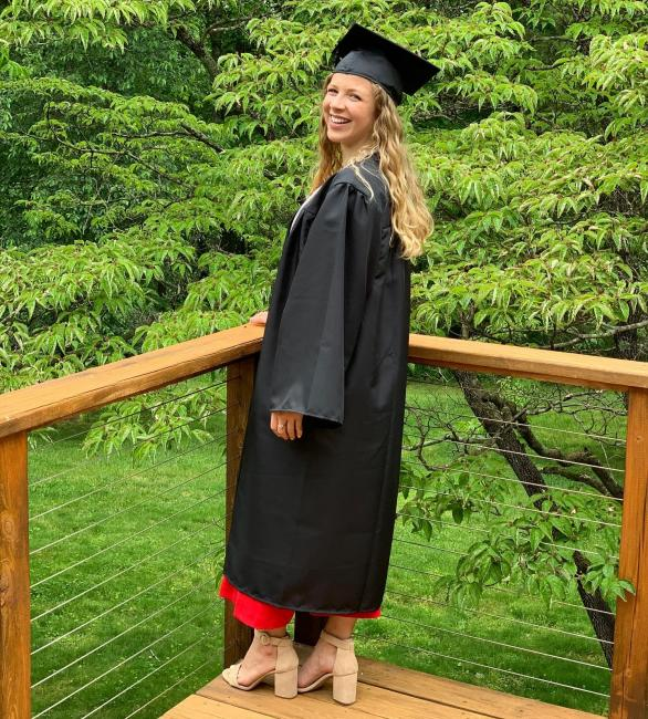 smiling graduate posing for picture on porch