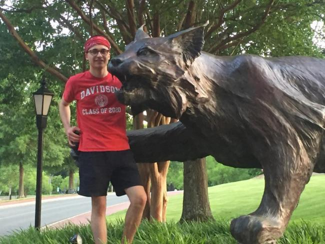 student poses next to wildcat statue