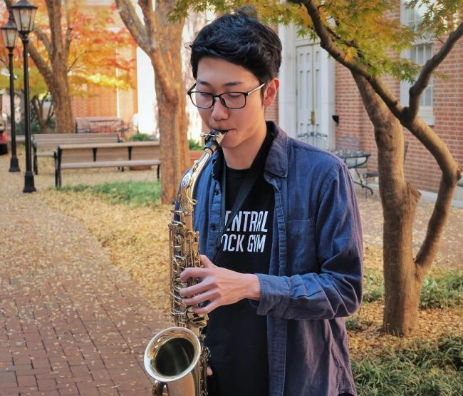 A senior saxophone player playing outdoors