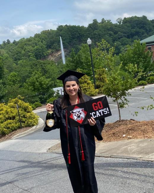graduate with champagne and a Davidson sign
