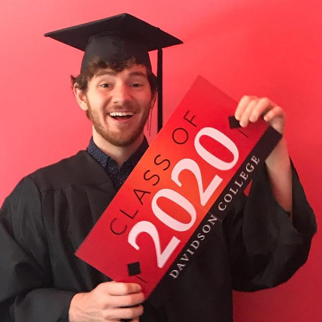 graduate holding up class of 2020 sign