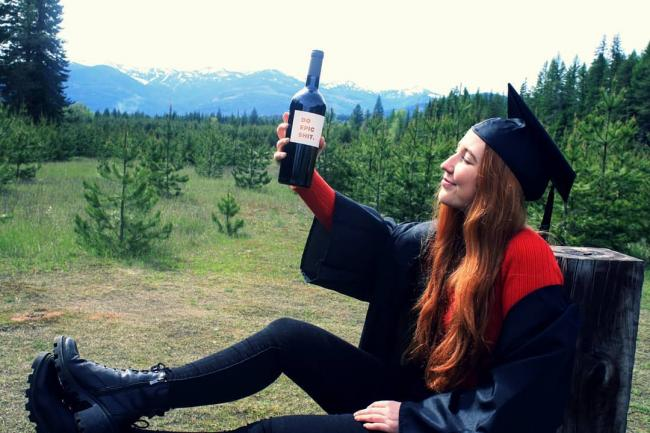 graduate raising a wine bottle to the sky