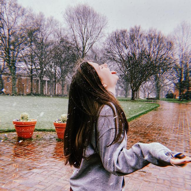 student catches snowflakes on her tongue