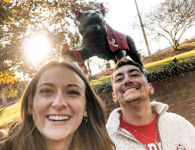 two students smiling in front of wildcat statue