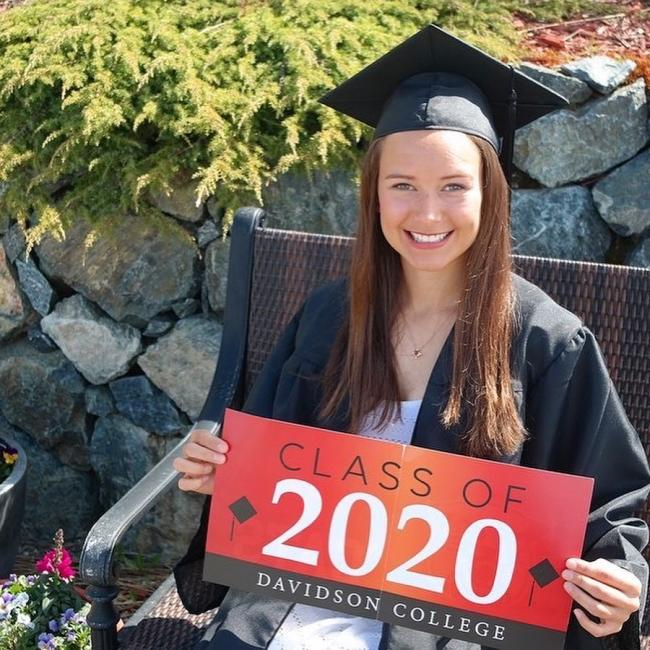 graduate holding a class of 2020 sign