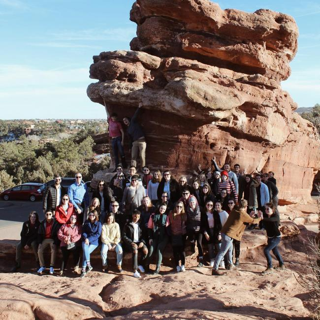 Chorale gathers for picture next to giant boulder in Colorado