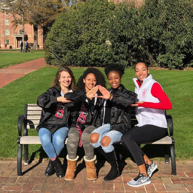 group of Upsilon Mu members sitting on a bench