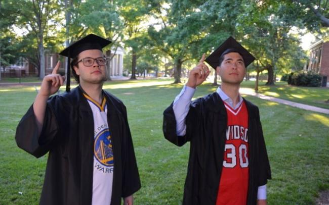two graduates in basketball jerseys pointing to the sky