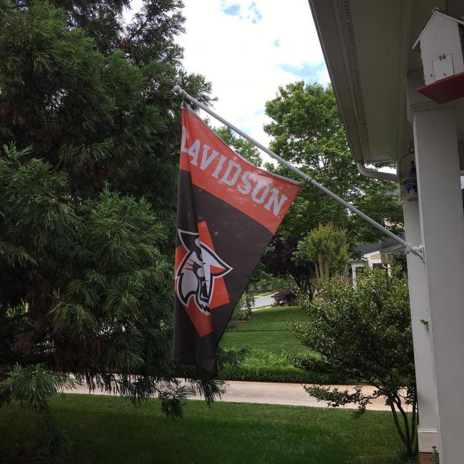 Davidson flag hanging off the side of a house surrounded by trees