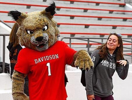 student and mascot posing together