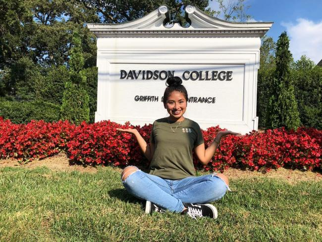 student sitting on the grass in front of the Davidson College sign