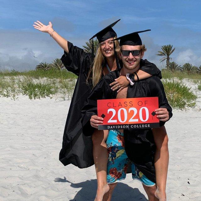 two graduates at the beach together