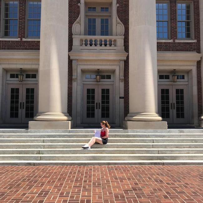 compsci student seated on the steps of college building