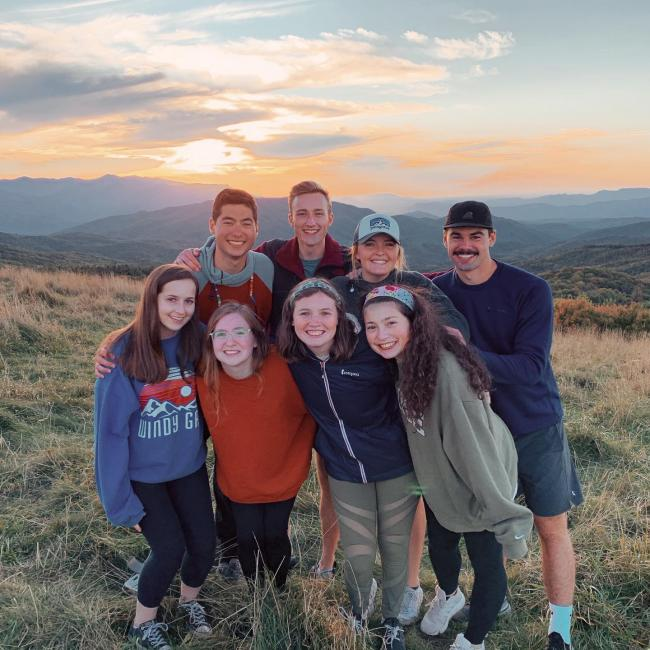 group poses for picture on the hills at sunset