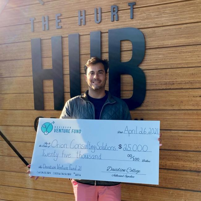 Owen Bezick '21 Claims Prize Check in Front of Hurt Hub