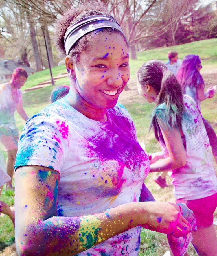 Student is covered in colorful powders during Holi celebrations