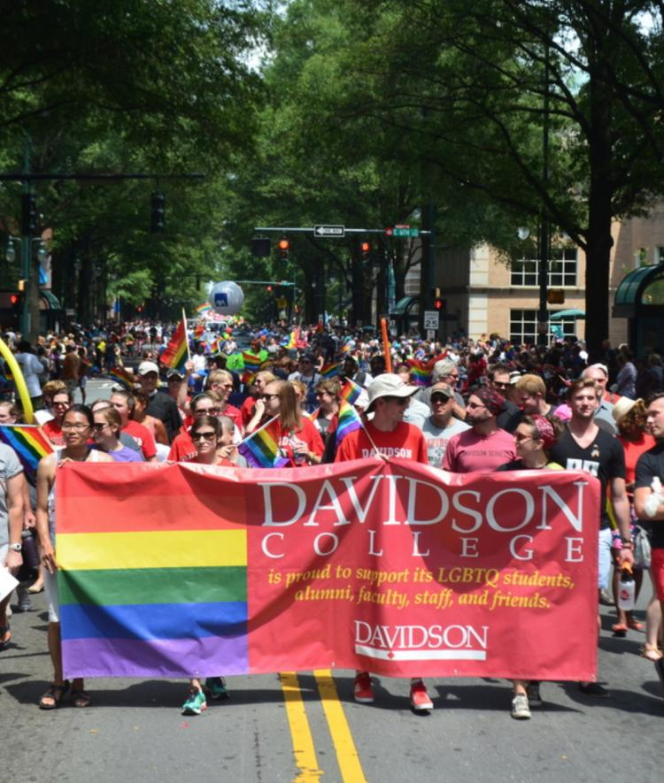 Davidson people hold up a banner that says the college supports LGBTQ members of the community during Pride