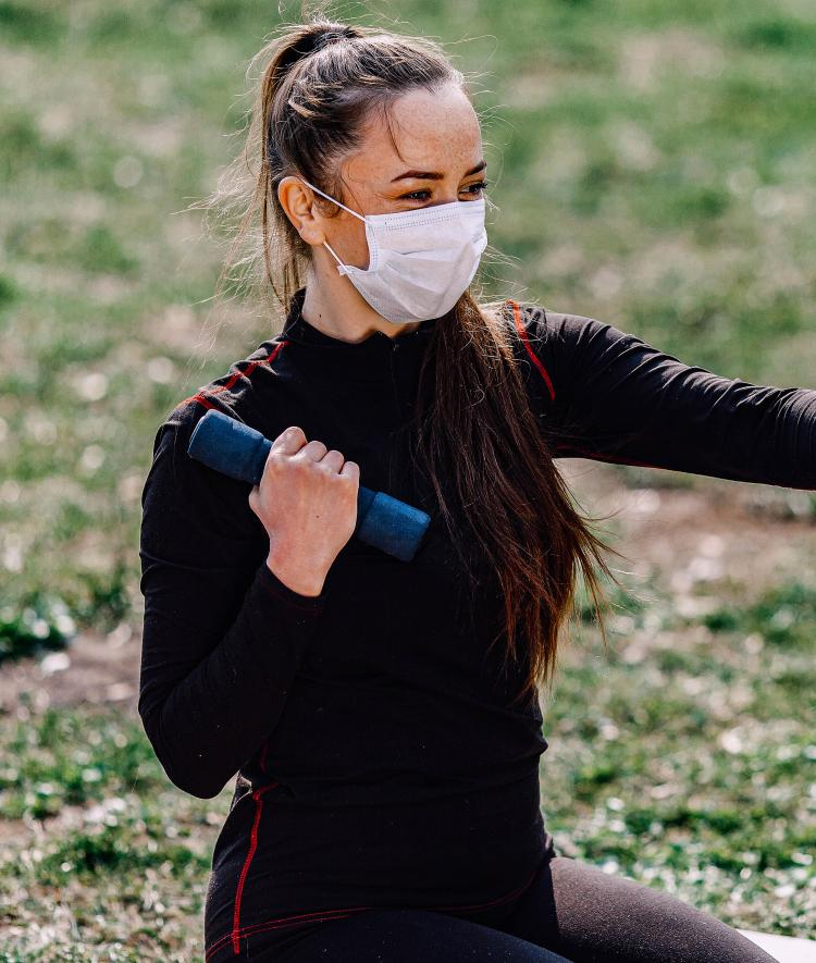 Woman Lifting Weights Outside Wearing Masks