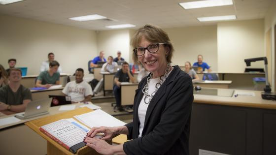Prof. Roberts smiles at camera while leading class from podium