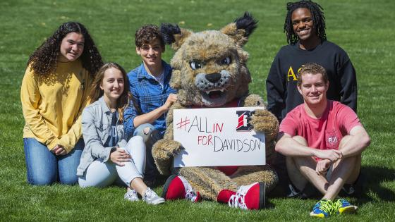 Lux and students sit on grass with sign reading #AllInForDavidson