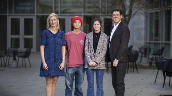 Scholars Michael Yen '23 and Georgia Morris '23  standing with scholarship founders Alison Hall Mauzé '84 and Mike Mauzé '85 in front of Wall building