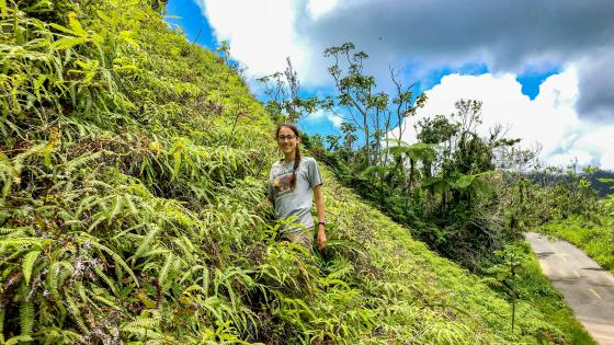 Lydia Soifer stands on a hill covered in vegetation