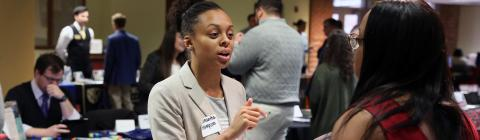 Law school recruiter talks to student at her booth