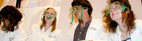Four students wearing lab goggles