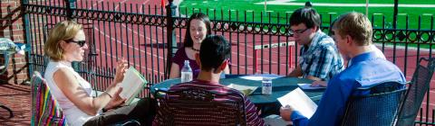 Prof. Neumann leads class at an outdoor table with the track and football field in the background