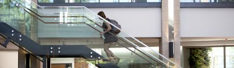 Student goes up Wall Center glass staircase
