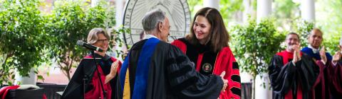 Carol Quillen hugs faculty member at commencement