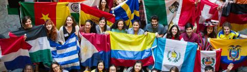 Students hold flags from many different countries