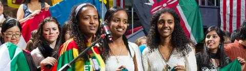 Students hold Ethiopian flag while students around them hold other international flags