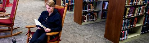 Student Reads Book in Library Rocking Chair