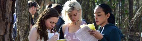 Three students look at analysis paperwork for environmental class assignment