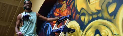 Stewy Robertson '15 with can of spray paint, working on mural