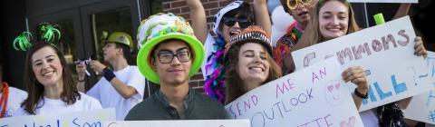 Group of Students Hold Up Funny Signs at Orientation
