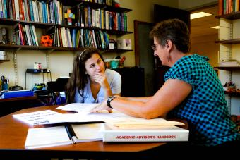 Prof. Molinek sits in her office with student looking at printed materials