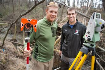 Prof. Brad Johnson and student stand in field with research equipment