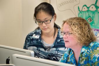 Prof. Heyer and a student look at data on a desktop computer in a lab