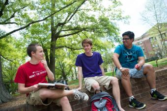 Three students sit on a brick wall, one holding a textbook and discussing
