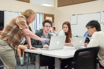 Professor Heyer stands near table and talks to three students who are using laptops in her class