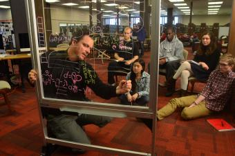 Professor Tim Chartier writes on a glass white board while leading a class to a group of students in the library
