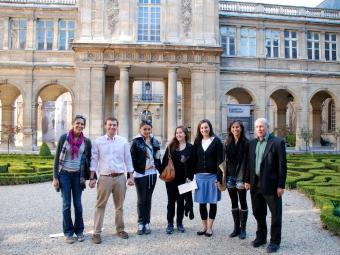 Group of six students and their professor stand in front of Musee Carnavalet in Paris