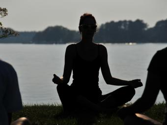 Silhouette of  woman in front of lake doing a yoga pose