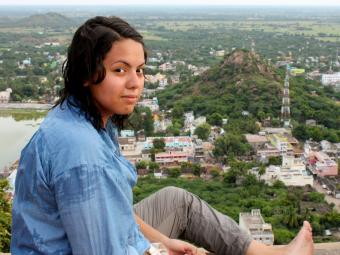 Student sits on a wall that allows a panoramic view of an Indian town