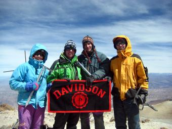 Four students in hiking gear stand atop a mountain in Peru holding a Davidson flag
