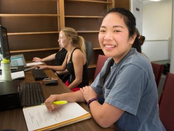Student smiles at camera in a psychology lab while her peer does research on the computer in the background